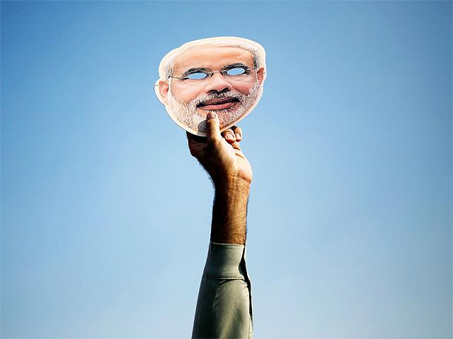 a-supporter-holds-up-a-mask-of-modi-during